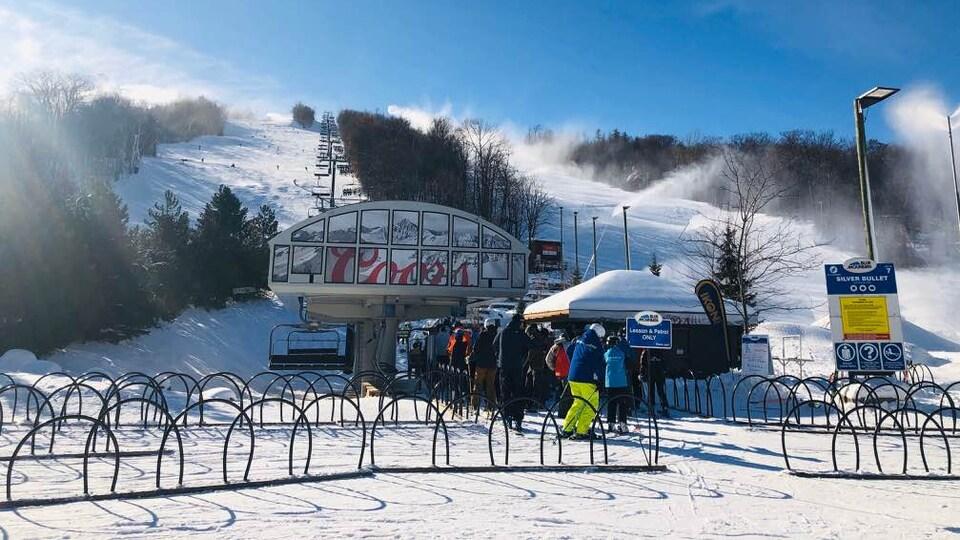 Des skieurs attendent avant de prendre un télésiège.