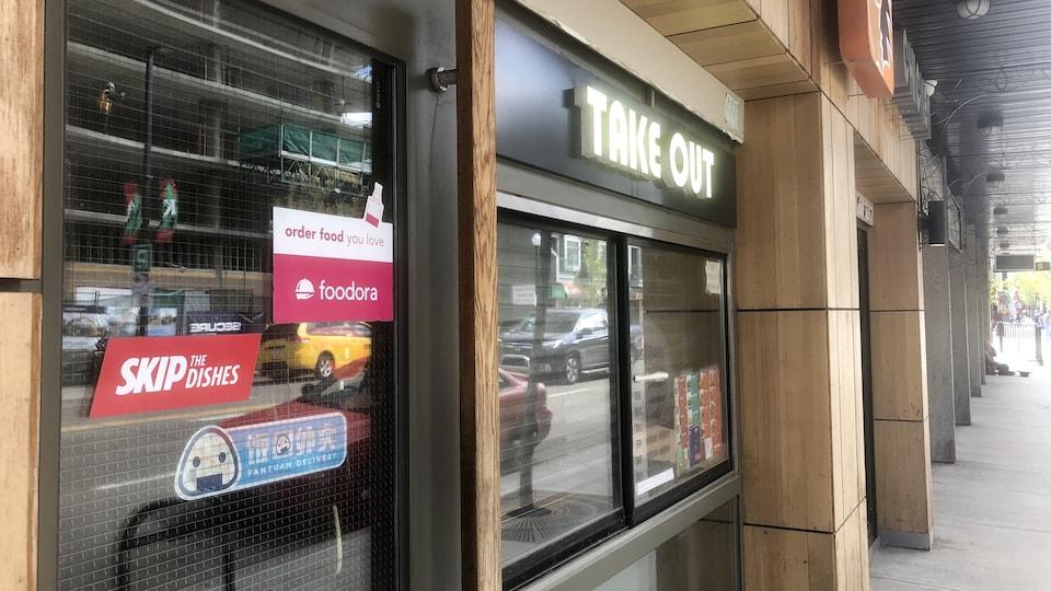 Devanture d'un restaurant. Sur la porte, il y a des autocollants d'entreprises de livraison comme Foodora et Skip The Dishes.