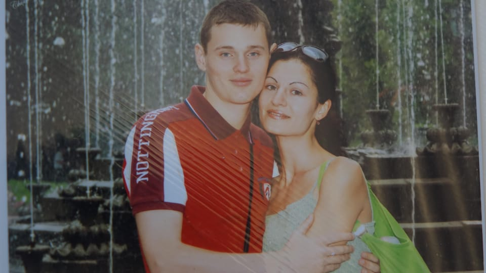 Un jeune couple enlacé regarde la caméra.