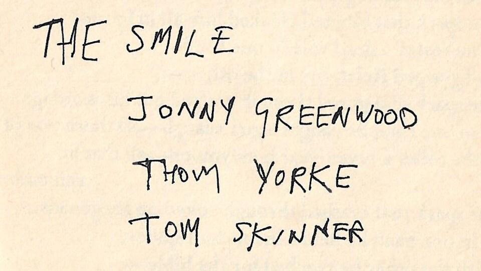 Texte écrit à la main où on peut lire The Smile, Jonny Greenwood, Thom Yorke et Tom Skinner