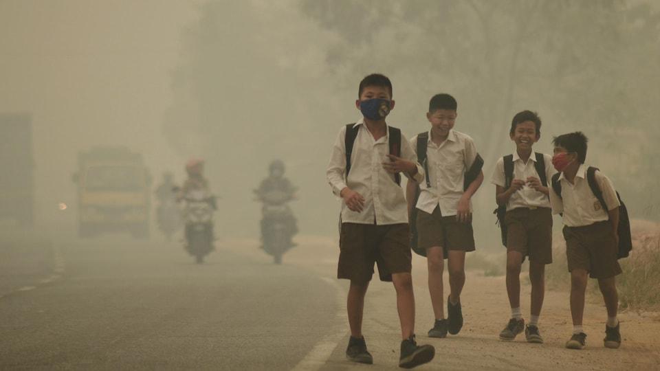Des jeunes en Indonésie se rendent à pied à l'école malgré un smog épais.