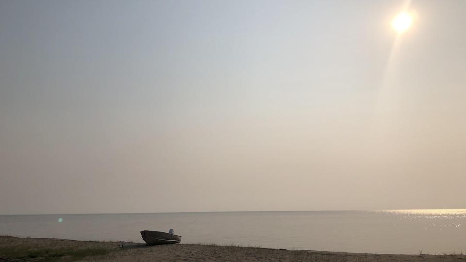 Une fumée diffuse recouvre une plage et un cours d'eau.