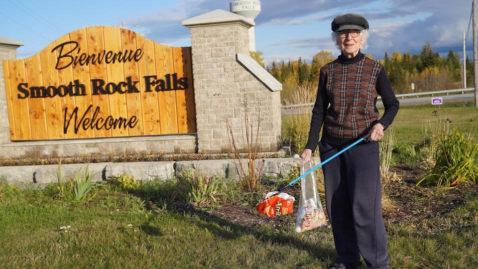 Une dame avec un sac de chips devant la pancarte de Smooth Rock Falls.