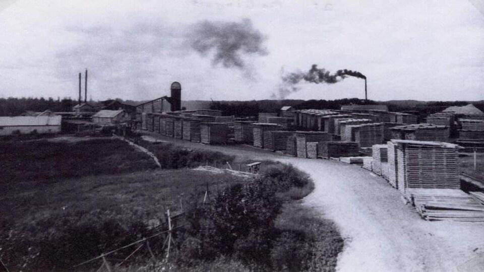 Le village de McInnis dans les années 50. On y voit les deux cheminées à l'extrémité gauche, à droite la pile de bran de scie.