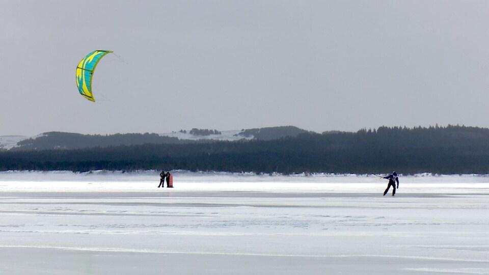 Une voile tire un participant sur la glace.