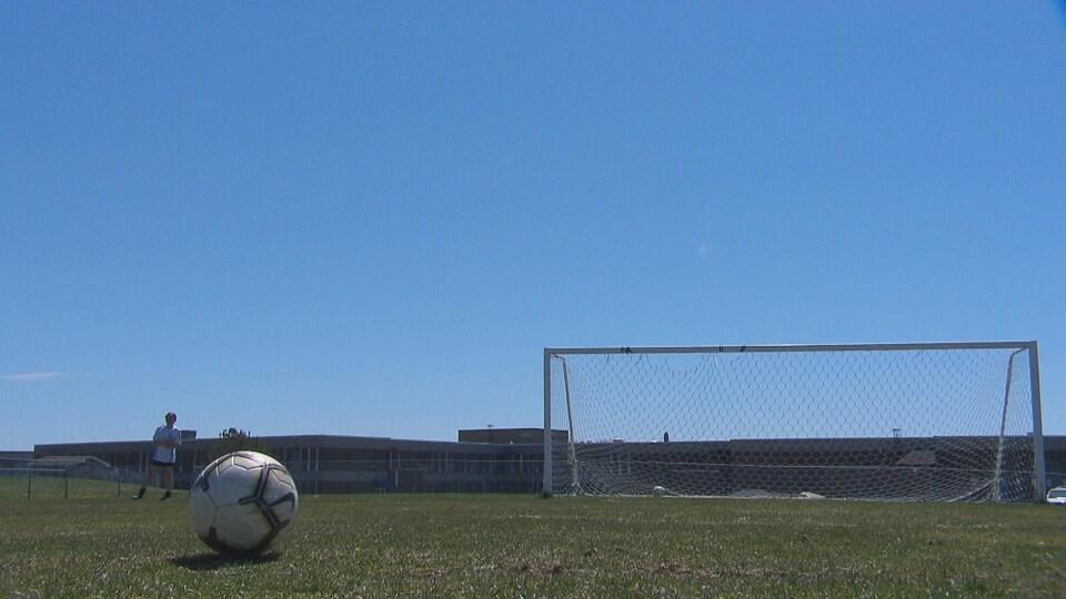Un ballon de soccer sur le sol devant un filet