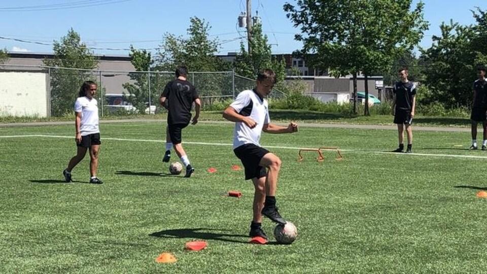 Des jeunes en train de jouer au ballons soccer.
