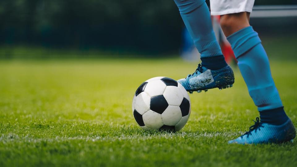 Plan au dessous des genoux d'un joueur de soccer, qui a le pied sur un ballon.