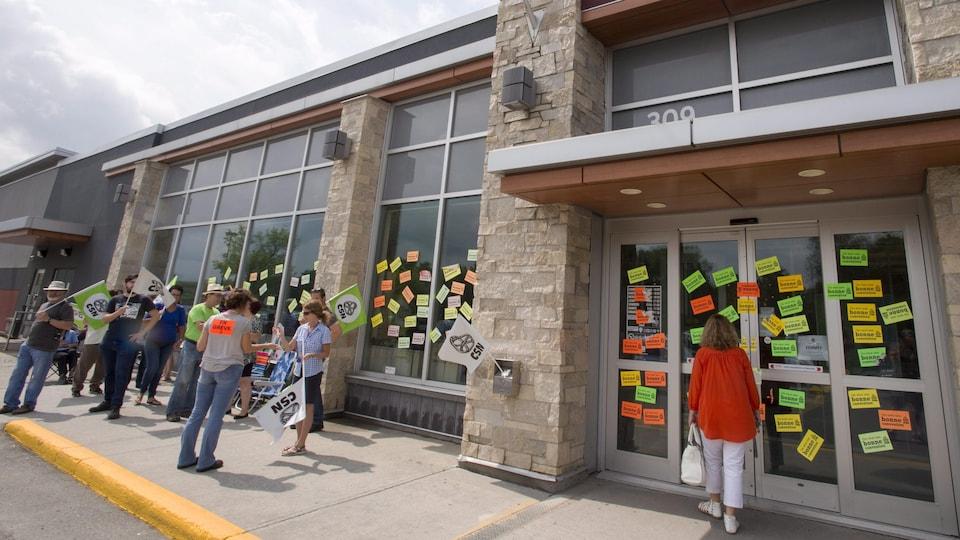 Une cliente se bute à des portes fermées devant un magasin de la SAQ pendant que des syndiqués en grève arborent des pancartes à Rosemère, en banlieue de Montréal