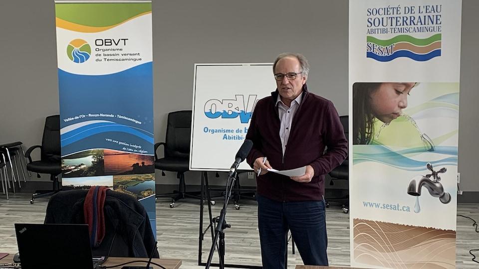 Serge Bastien parle au micro devant des affiches de l'Organisme du bassin versant du Témiscamingue et de la Société de l'eau souterraine Abitibi-Témiscamingue.