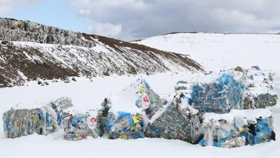 Des ballots de matériaux recyclables stockés à l'extérieur.