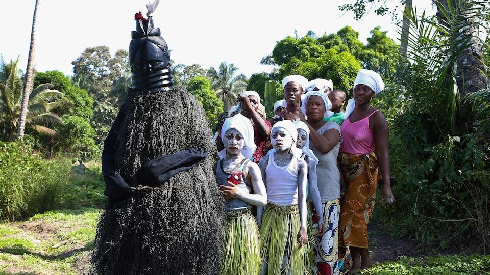 Des jeunes filles couvertes d'une peinture blanche sur tout le corps et en pagne suive une personne déguisée sous un masque.