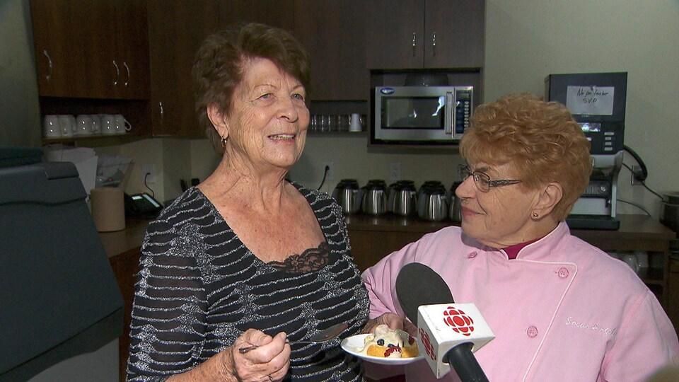 Augustine Harrisson et Soeur Angèle en entrevue avec Radio-Canada, dans la cuisine de la Résidence des Bâtisseurs.