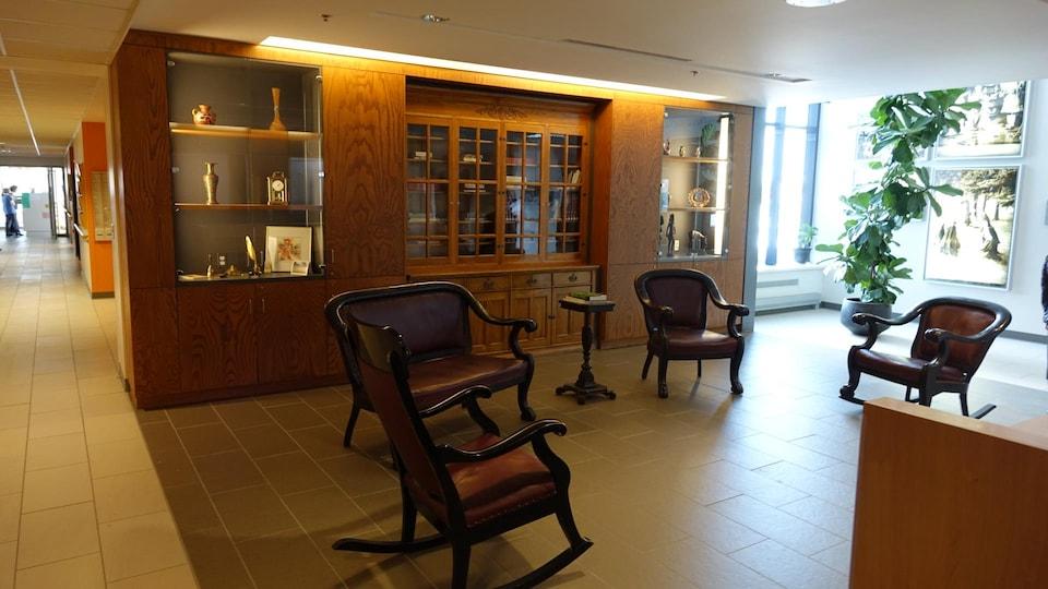 Des fauteuils devant une étagère vitrée qui abrite divers objets