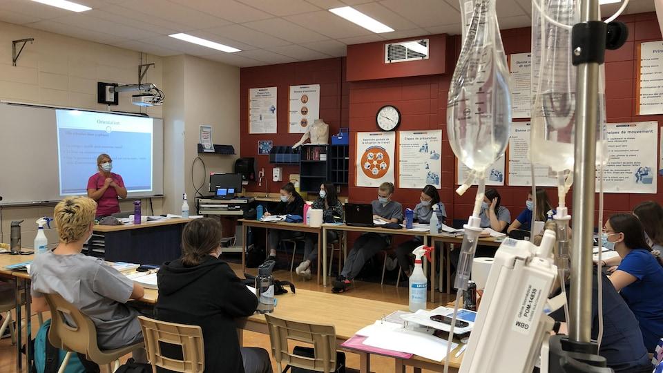Des étudiants en soins infirmiers assistent à un cours derrière un soluté.
