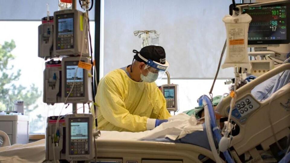 Un infirmier praticien s'occupe d'un patient dans une unité de soins intensifs.