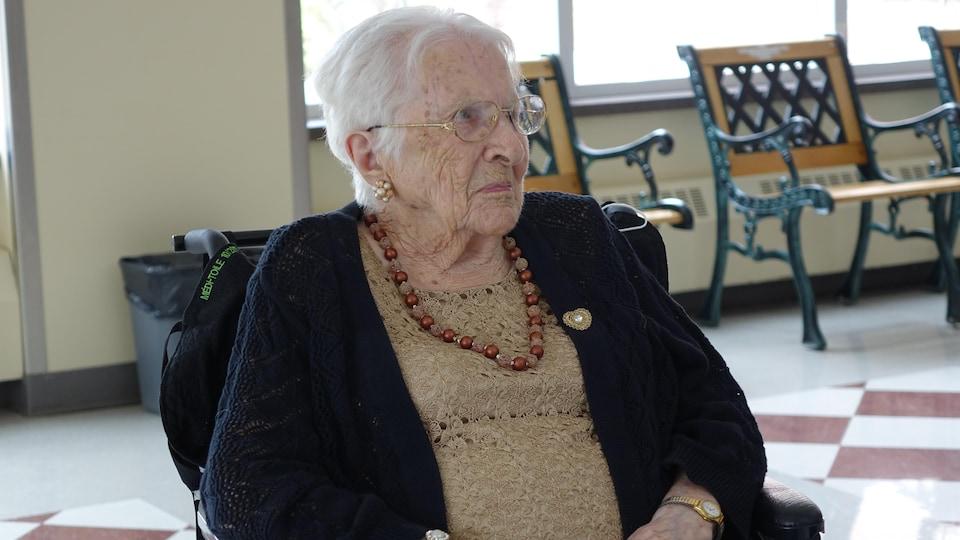 une femme âgée assise dans un chaise roulante.