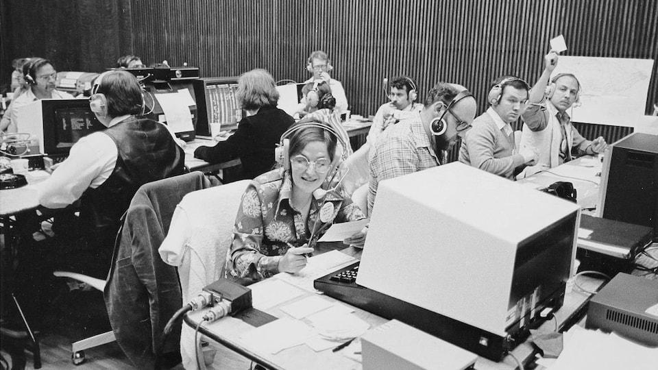 Une équipe de Radio-Canada s'active dans un studio où sont installées quelques rangées de tables avec de l'équipement informatique.