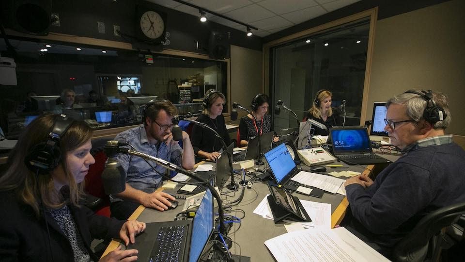 L'un des studios radio de Radio-Canada, plusieurs personnes derrière leurs ordinateurs.