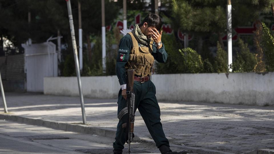 Bir Afgan askeri, yüzünü Kabil sokaklarında saklıyor.