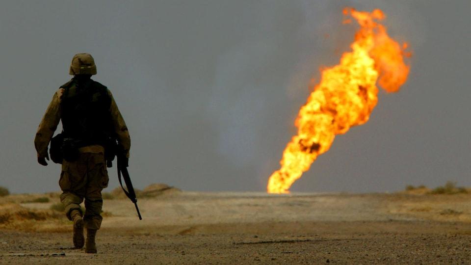 Un soldat américain marche en solitaire vers un puits de pétrole qui brûle.