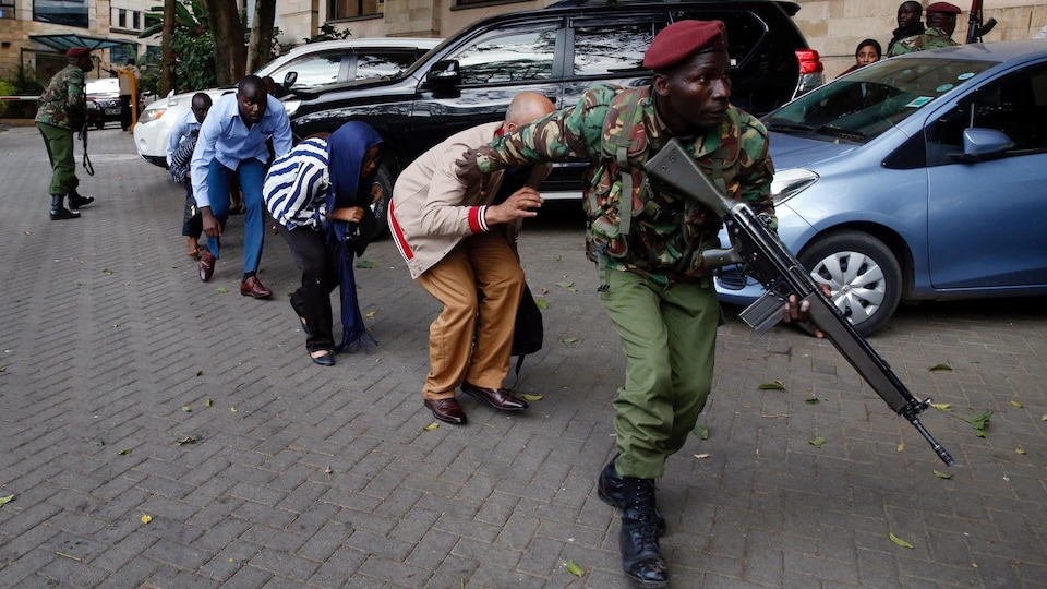 Un soldat escorte des civils qui tentent de fuir l'hôtel DusitD2.