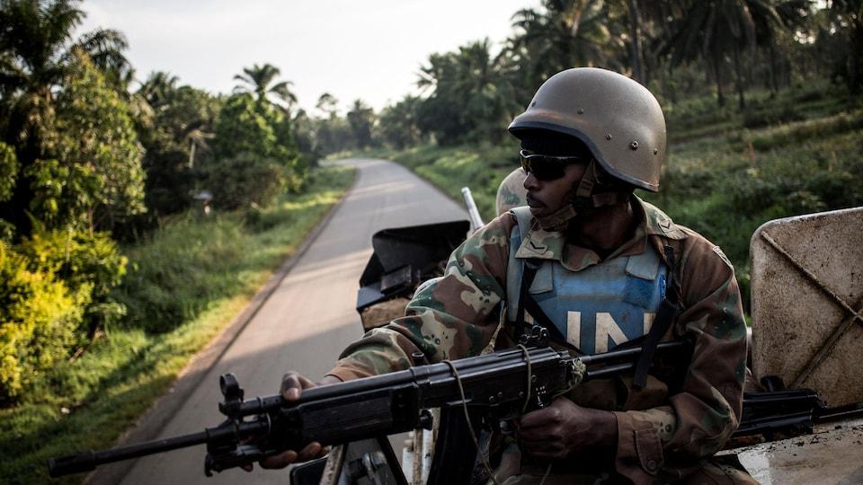Un soldat de l'ONU assis sur un véhicule arme à la main.