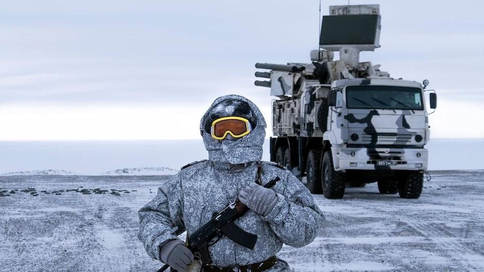 Le soldat est habillé chaudement. On ne voit que ses lunettes de ski dépasser de son capuchon. Il tient un fusil contre lui.