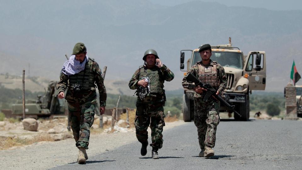 Des soldats marchant devant un véhicule militaire.