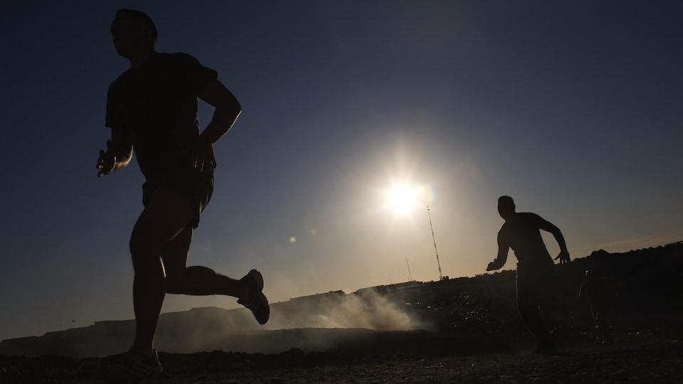 Deux soldats courent sur un sentier poussiéreux.