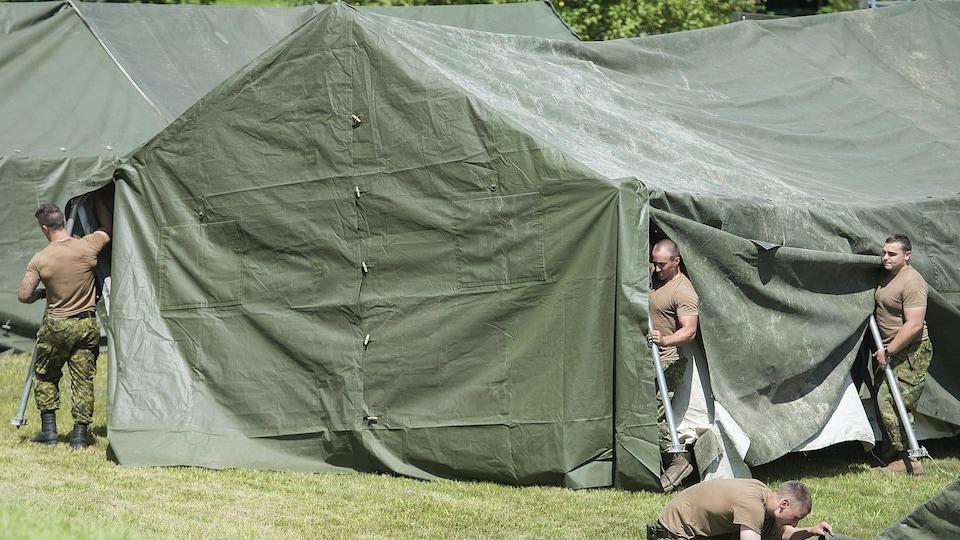 Trois militaires, dont deux tiennent des poteaux pour tendre une toile, achèvent le montage d'une tente au poste frontalier de Saint-Bernard-de-Lacolle, au Québec.