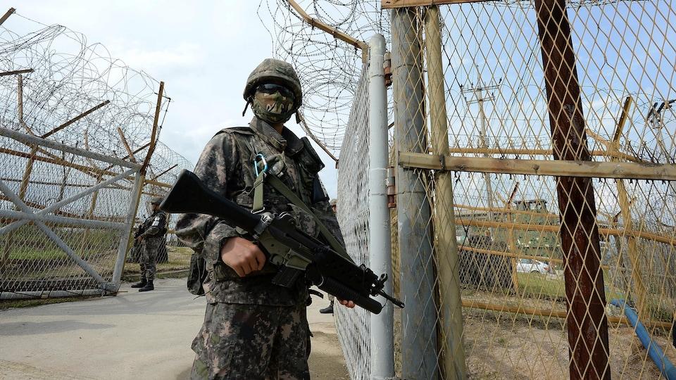 Un soldat ayant la figure recouverte d'un masque tient une mitraillette.