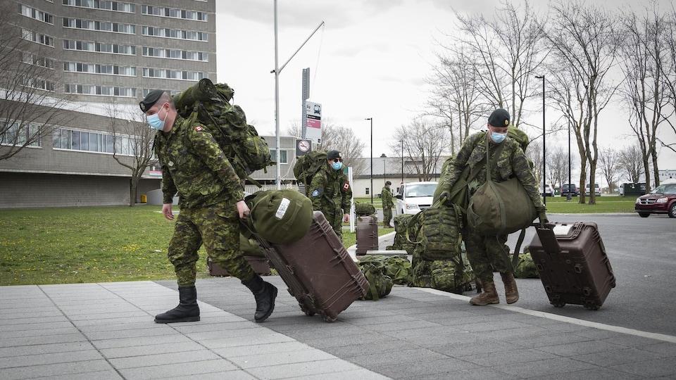 Un groupe de soldats en uniforme de combat, portant un masque chirurgical, arrivent au centre de formation avec leurs bagages.