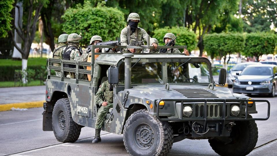 Des soldats descendent d'un véhicule de transport.