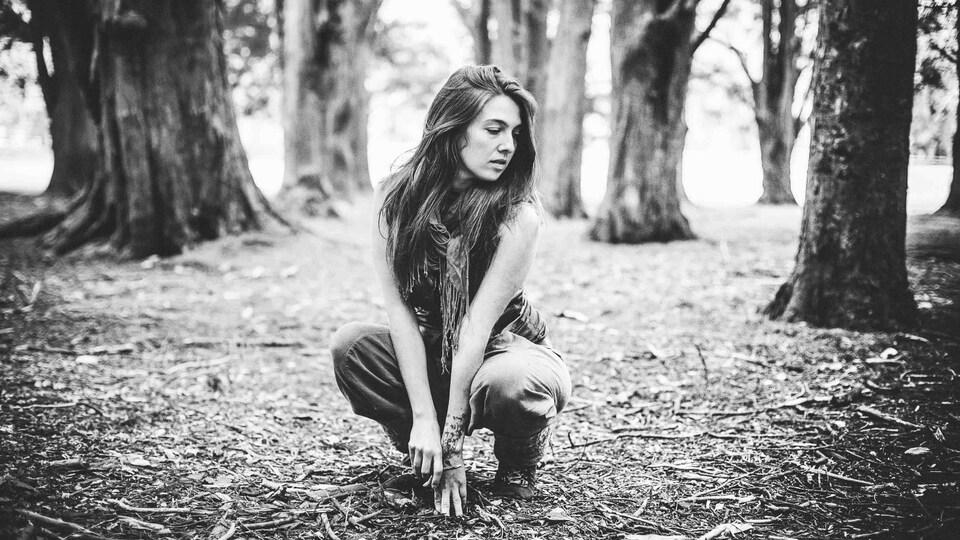 Une femme est accroupie entre des arbres dans une forêt, en noir et blanc.