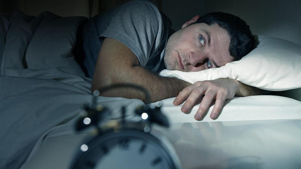 Un homme les yeux ouverts dans la nuit.