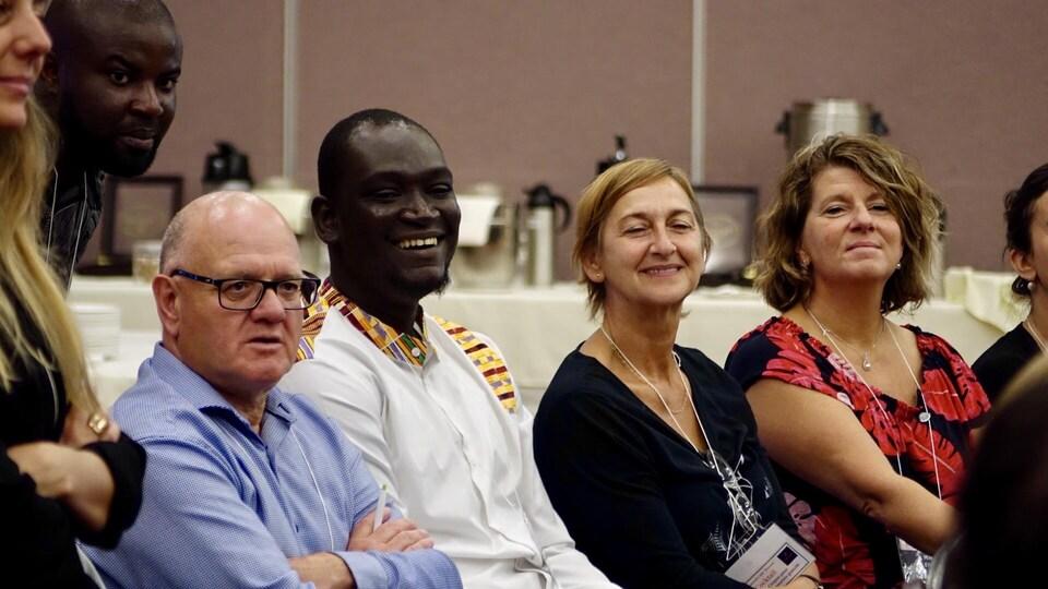 Gros plan sur quatre participants souriants assis dans une salle de conférence.