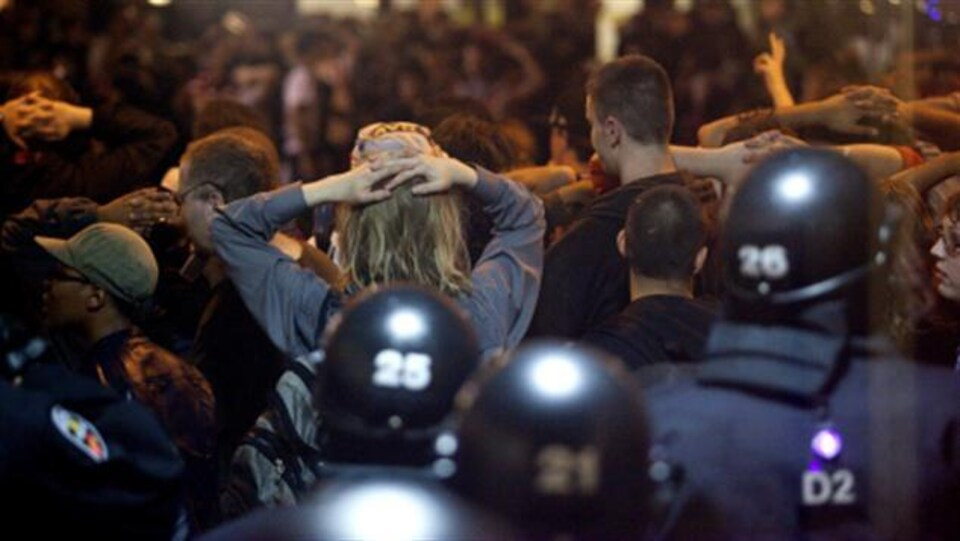 Des civils arrêtés par la police, les mains sur la tête.