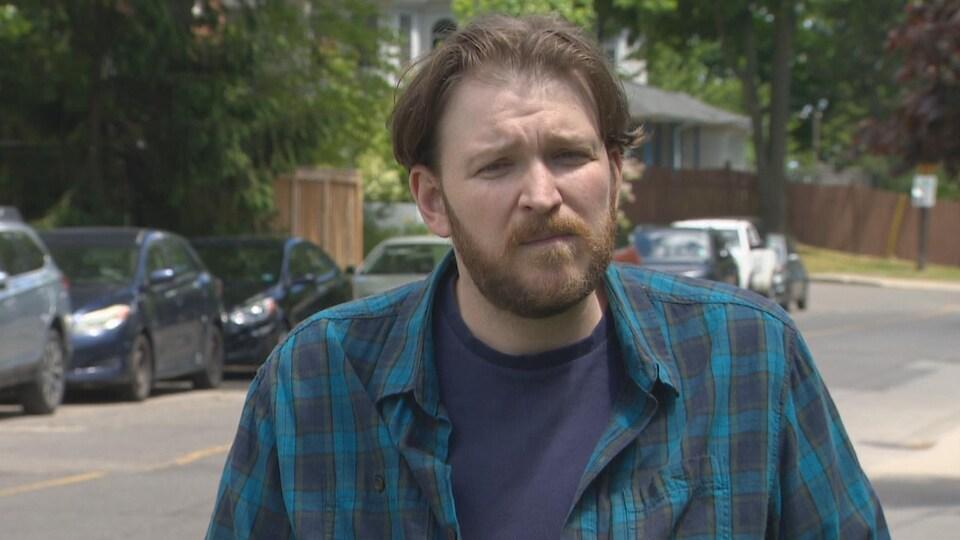 Un homme avec une barbe dans la rue.