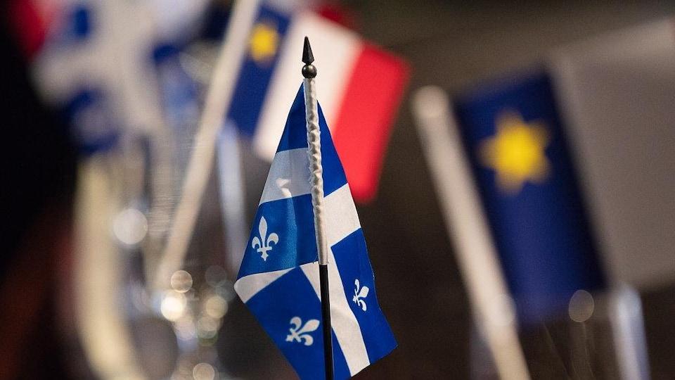 Un drapeau québécois avec en fond un drapeau acadien.