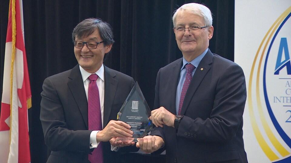 On voit le p.-d.-g. de l'aéroport Pearson au côté du ministre fédéral des Transports, Marc Garneau en train de tenir le trophée du Conseil international des aéroports