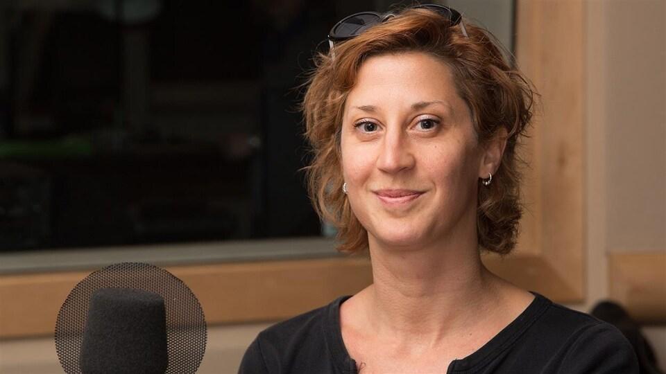 Sonia Cotten devant un micro assise dans un studio de radio.