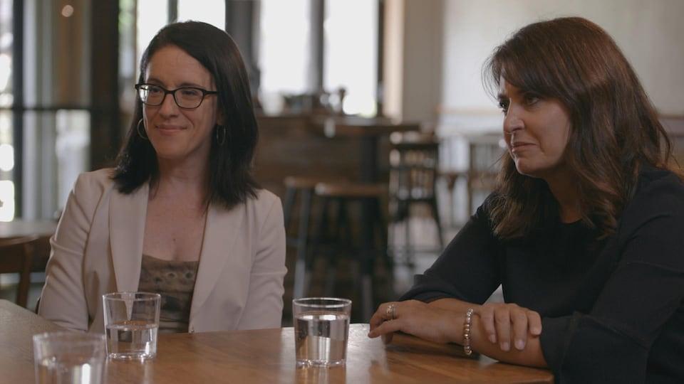 Les deux femmes sont assises devant une table.