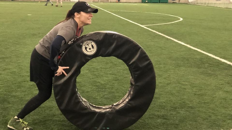 Une femme tient un anneau en mousse sur un terrain de football.
