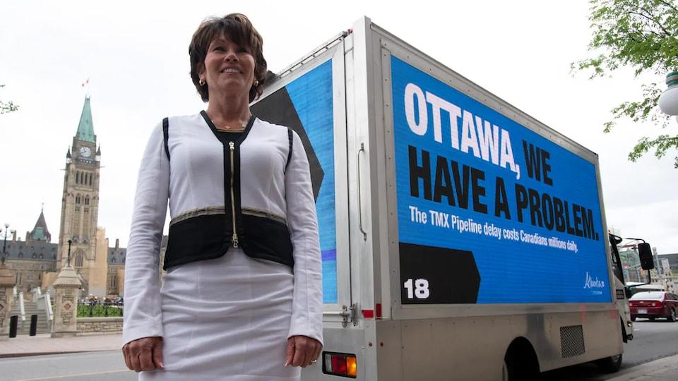 Sonya Savage est debout devant un camion qui porte un grand écriteau disant « Ottawa, nous avons un problème », sur la colline du Parlement.