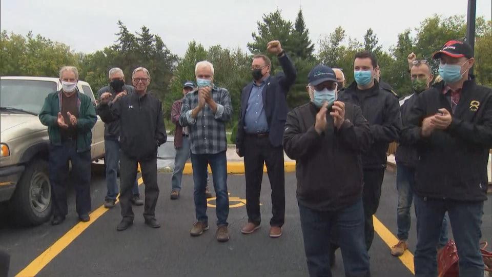 Plusieurs personnes portant le masque applaudissent ou brandissent le point.