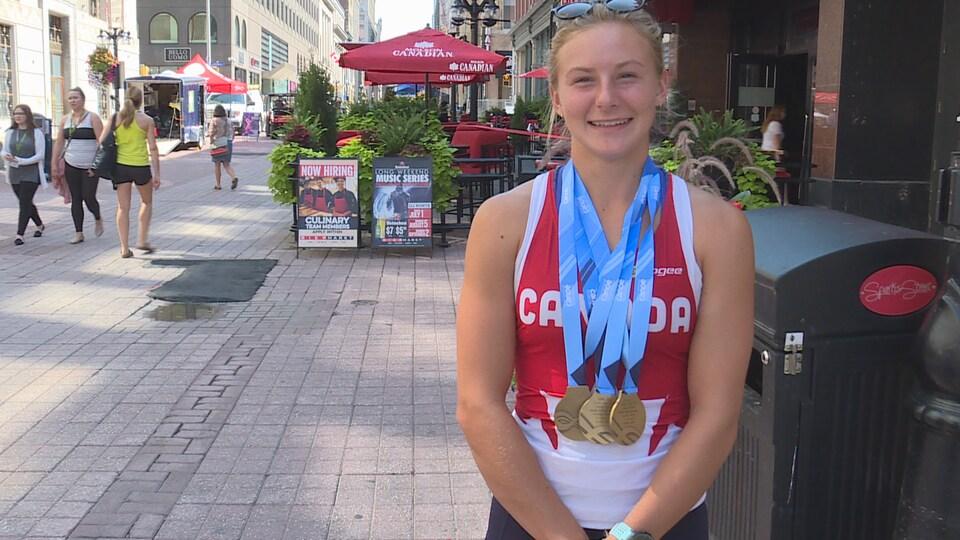 Sophia Jensen dans une rue piétonne d'Ottawa vêtue d'un maillot Canada, trois médailles d'or au cou.