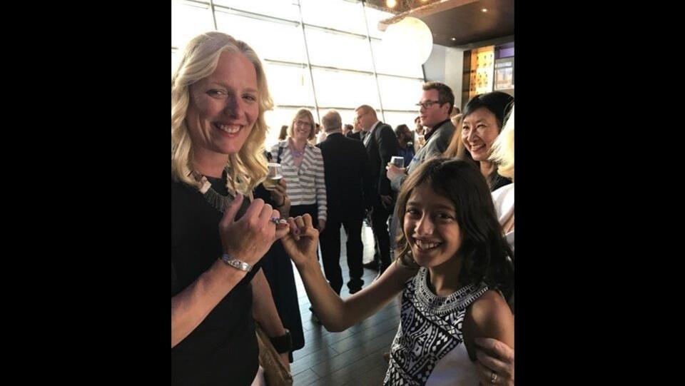 La ministre et la jeune fille se serrent le petit doigt.