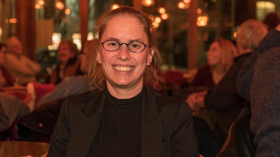 On voit Sophie Breton de face, assise au bar L'Barouf