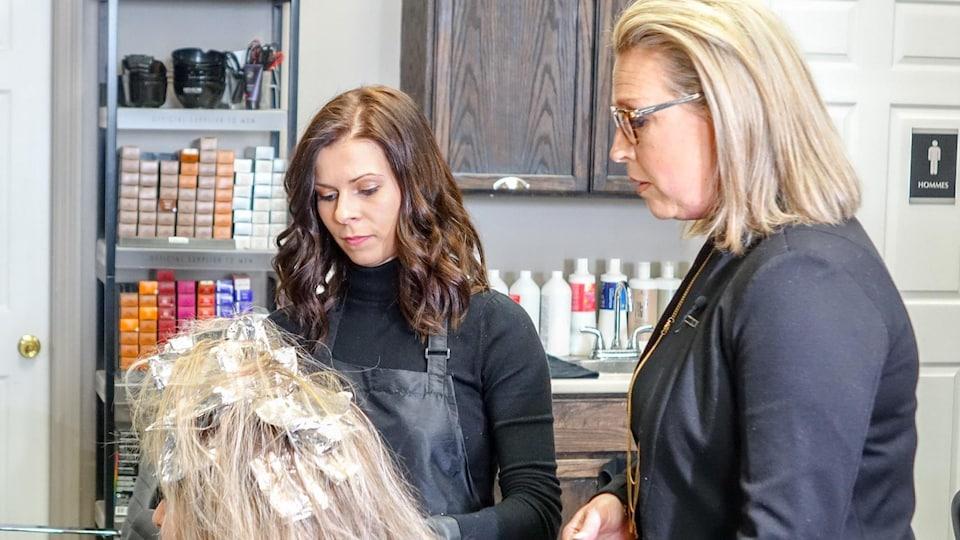 Sophie Cadorette, propriétaire du salon de coiffure Imagine'Hair à Lévis, discute avec une coiffeuse et une cliente